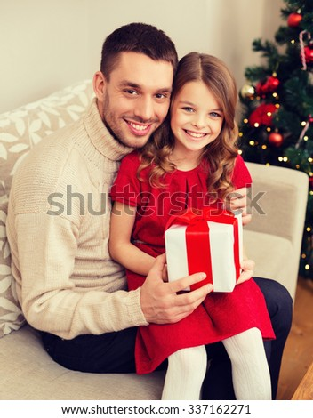 family, christmas, x-mas, winter, happiness and people concept - smiling father and daughter holding gift box - stock photo