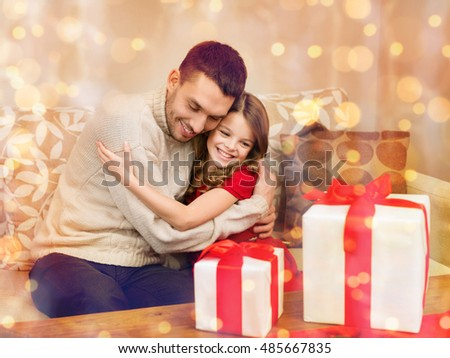 family, christmas, x-mas, winter, happiness and people concept - smiling father and daughter hugging