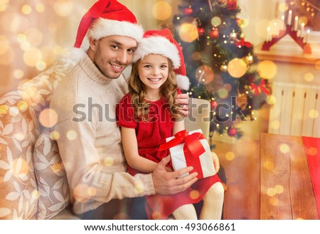 family, christmas, x-mas, winter, happiness and people concept - smiling father and daughter in santa helper hats holding gift box