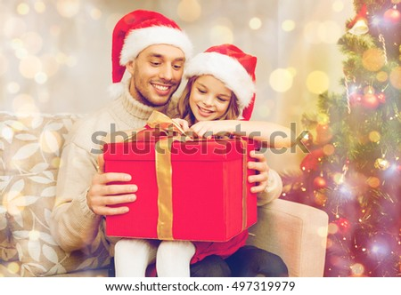 family, christmas, x-mas, winter, happiness and people concept - smiling father and daughter in santa helper hats opening gift box