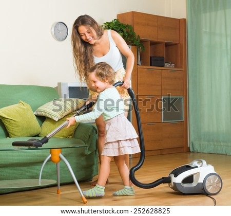 Family cleaning living room with vacuum cleaner  - stock photo