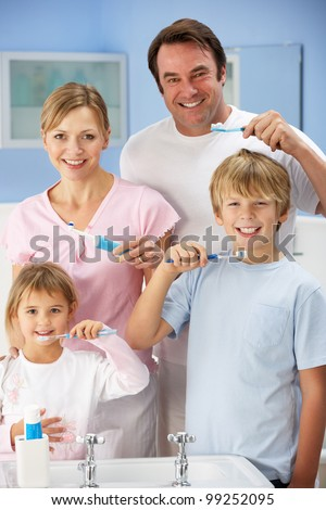 Family cleaning teeth together in bathroom - stock photo