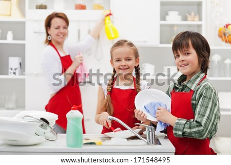 Family cleaning the kitchen and washing dishes - stock photo