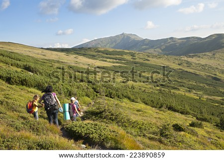 Family climbing green mountain in idyllic landscape - stock photo