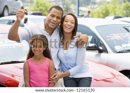 Family collecting new car from lot - stock photo