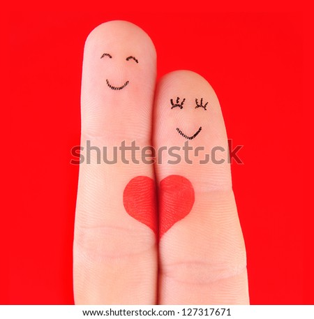 family concept - a man and a woman hold on the red heart, painted at fingers and isolated on red background - stock photo