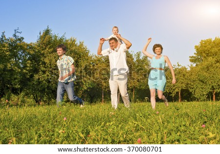 Family Concept and Ideas. Happy Family of Four Running Together Outside in Green Summer Forest. Horizontal Image Orientation