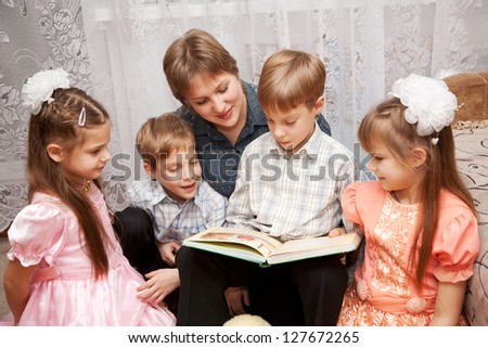 Family concept. Happy mother and four children reading a book. Big family. - stock photo