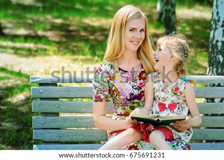 Family concept. Happy mother reading fairy tales with her little daughter in the park. Summer holidays.