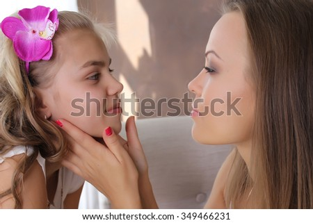 Family concept. Mom hugging daughter to face. She looks at her with great love. Blond - stock photo