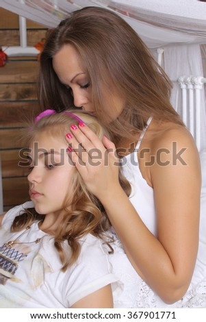 Family concept. Mom kisses the top of his beloved daughter. Family values.  - stock photo