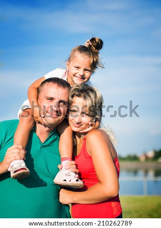 Family concept. Portrait of a happy family of three having fun together outdoors