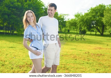 Family Concept. Young Caucasian Family  Together Outdoors Having a Walk in Park. Nature Background. Horizontal Shot