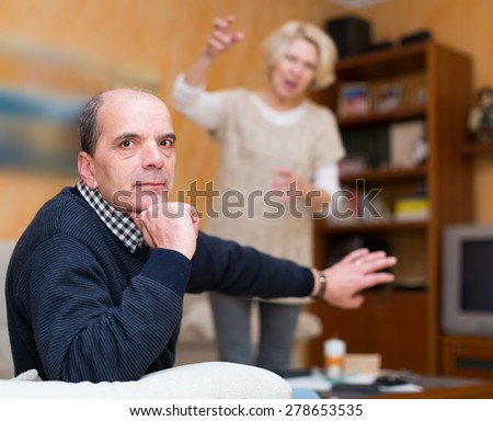 Family conflict. Aged spouses having quarrel in living room at home  - stock photo