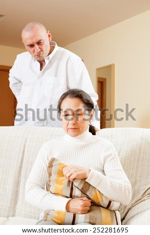 Family conflict. Middle-aged couple after quarrel in living room at home  - stock photo