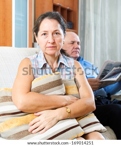 Family conflict. Portrait of sad woman against elderly man with newspaper at home - stock photo