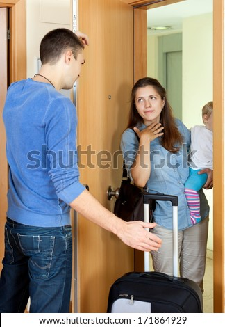 Family conflict. Sad guy against wife with baby in living room - stock photo