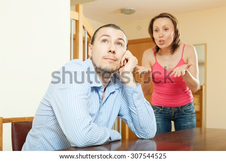 Family conflict. Sad man listening to his angry woman at home - stock photo