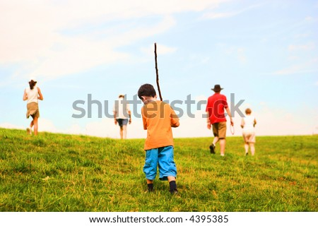 Family consisting of grandparents, son and grandchildren on and outdoor field adventure, hiking amongst the hills in a lovely summer's afternoon. - stock photo
