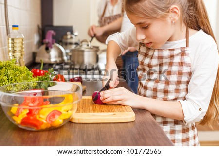 Family cooking background. Small girl cutting onion preparing salad at the kitchen counter - stock photo