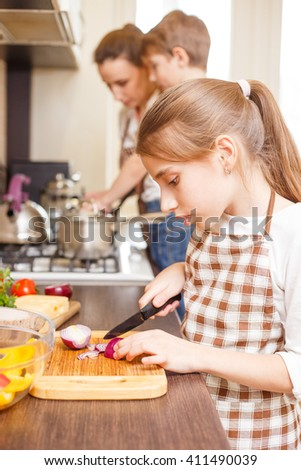 Family cooking background. Teen girl cutting onion on chopping board.