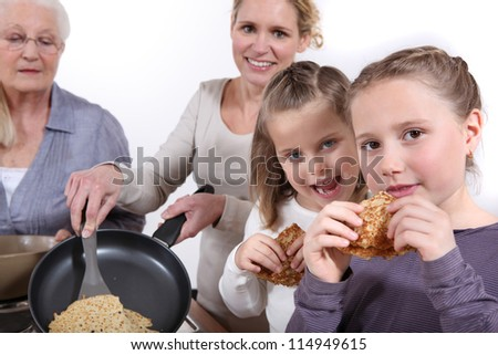 Family cooking pancakes - stock photo