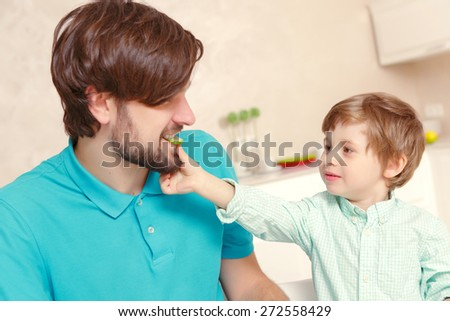 Family cooking. Portrait of a small son feeding his young father with a cucumber - stock photo