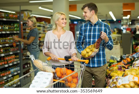 Family couple buying sweet fruits in local  shop