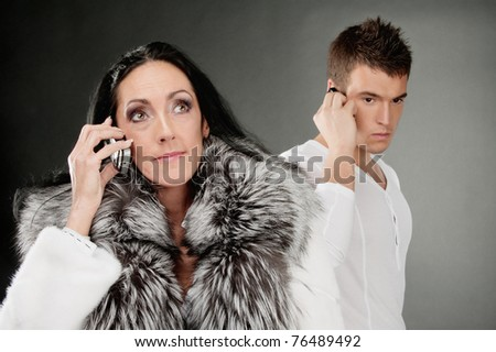 Family couple speak on mobile phones, on gray background. - stock photo