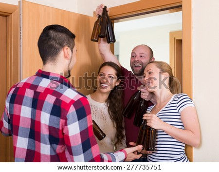 Family couple welcoming happy visitors with beer bottles at home - stock photo