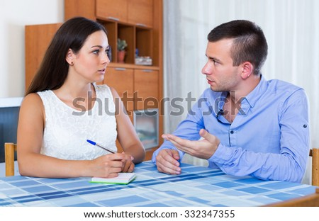 Family couple with money problems making shopping list 