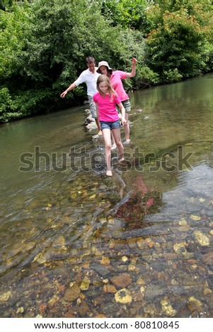 Family crossing river barefoot - stock photo