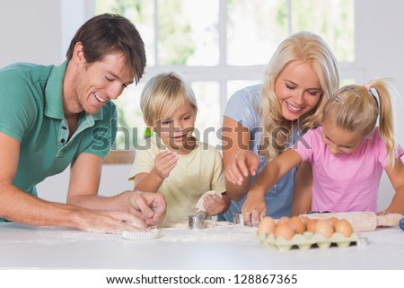 Family cutting the dough for cookies - stock photo