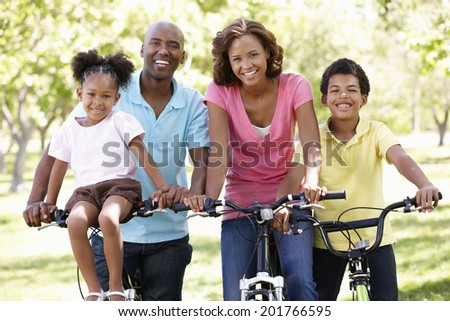 Family cycling in park - stock photo