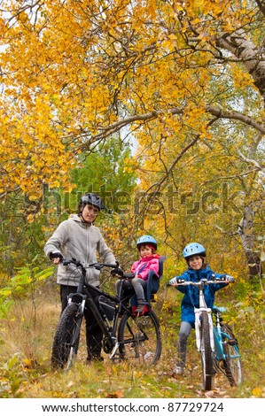Family cycling outdoors, golden autumn in park. Vertical photo