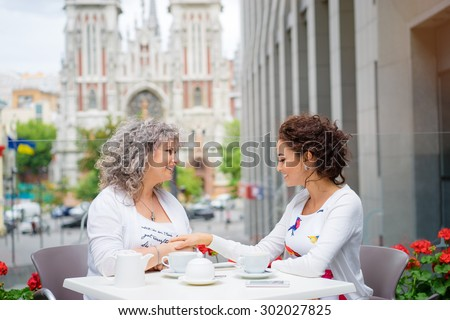 Family day. Aged woman and her adult daughter drinking coffee at sidewalk cafe. - stock photo