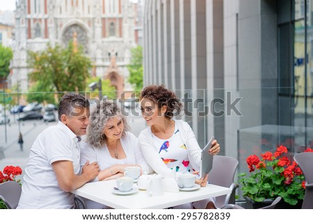 Family day. Elderly loving couple and their adult daughter using tablet computer together while sitting in sidewalk cafe. - stock photo