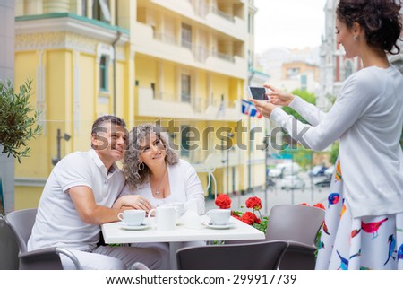 Family day. Middle aged couple embracing in cafe while adult daughter photographing them on smartphone. - stock photo