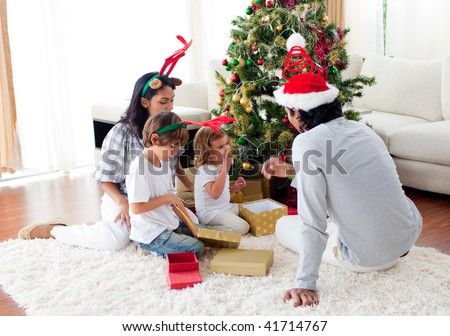 Family decorating a Christmas tree at home - stock photo