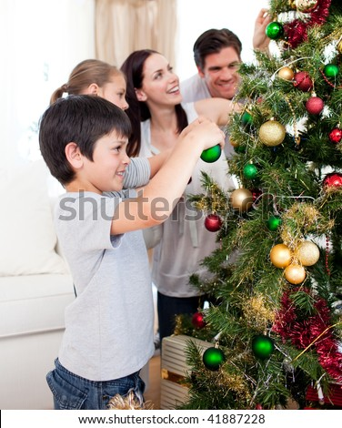 Family decorating a Christmas tree with boubles in the living-room - stock photo