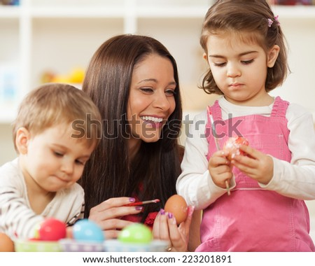 Family decorating Easter eggs - stock photo