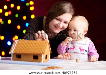 Family decorating gingerbread house at Christmas eve - stock photo