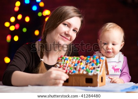 Family decorating gingerbread house on Christmas eve - stock photo