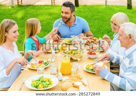 Family dining together. Top view of happy family of five people communicating and enjoying meal together while sitting at the dining table outdoors  - stock photo