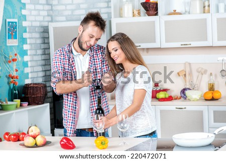 Family dinner. Attractive couple in love cooking and opens the wine in the kitchen while they cook dinner for a romantic evening. - stock photo