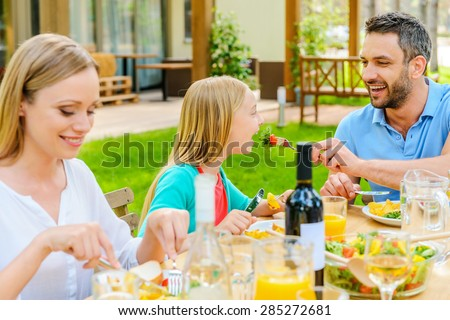 Family dinner. Happy young man feeding his daughter with salad while sitting together at the dining table  - stock photo