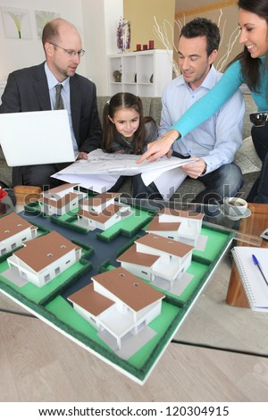 Family discussing a housing development with an architect - stock photo