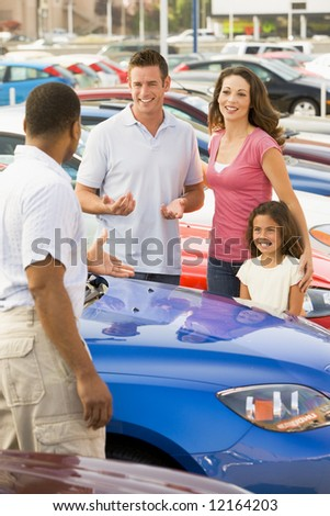 Family discussing new car with salesman on lot - stock photo