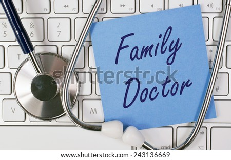 Family Doctor - blue note paper with stethoscope on keyboard - stock photo