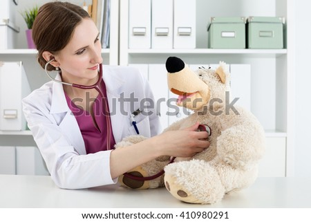 Family doctor examination. Beautiful smiling female doctor in white coat examine teddy bear with stethoscope to calm down and interest child. Playing with baby patient. Pediatrics medical concept - stock photo